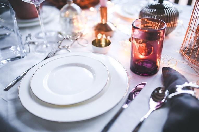 sto na kome se nalazi beli tanjir i pribor za jelo