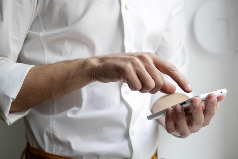 Čovek koji drži telefon u ruci