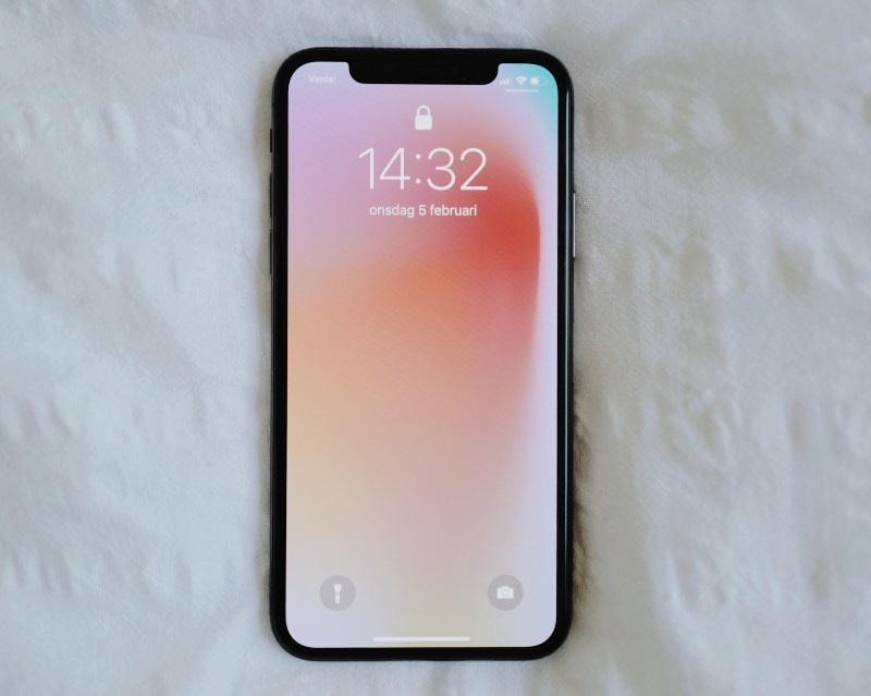 Iphone mobilni telefon na beloj posteljini