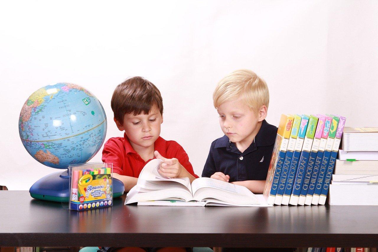 Dečaci koji sede za stolom i uče