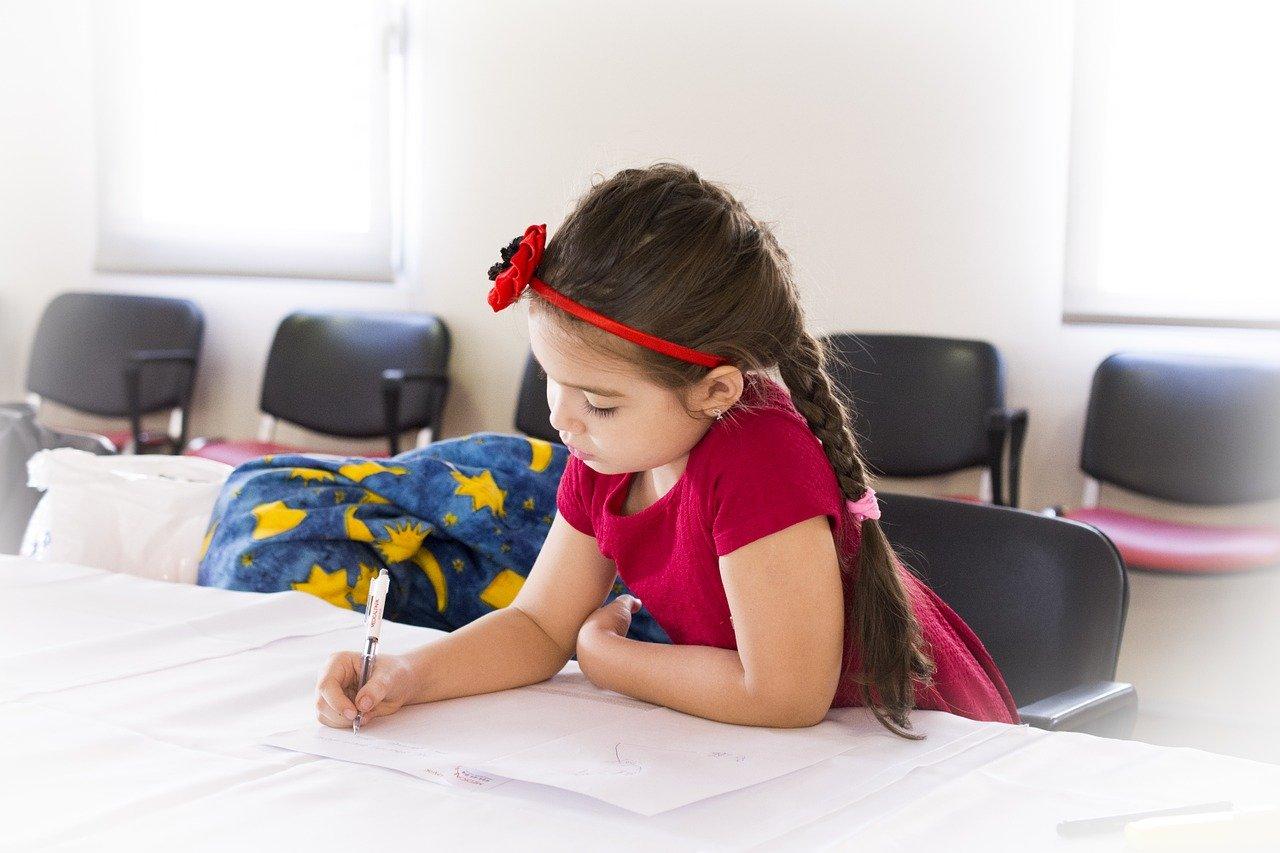 Devojčica koja sedi za stolom i uči
