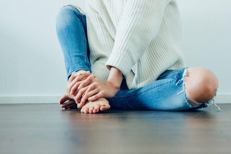 Devojka koja sedi na podu u farmericama i džemperu