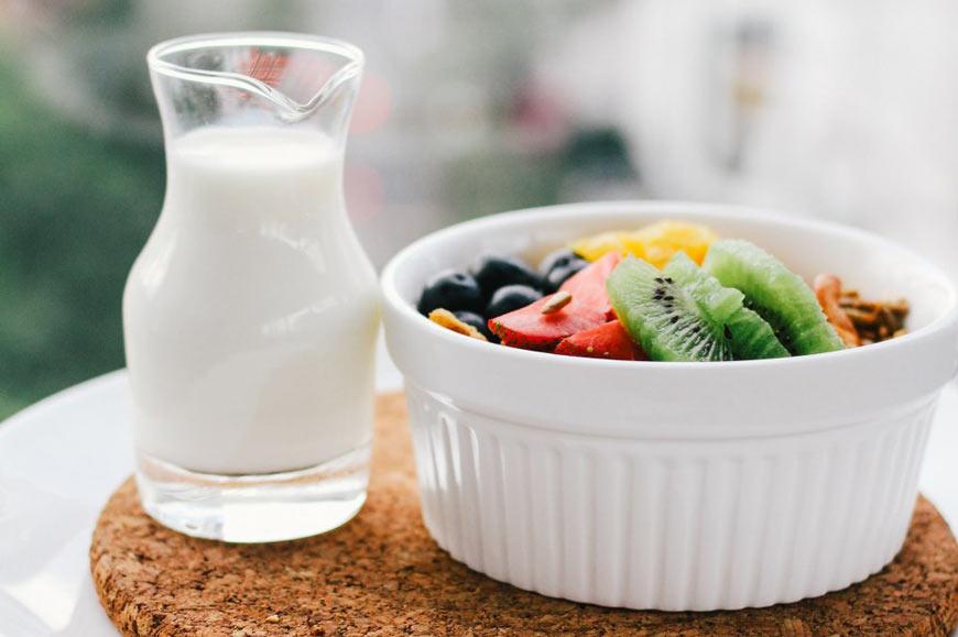 Prikaz mleka u tegli i činije voća na stolu
