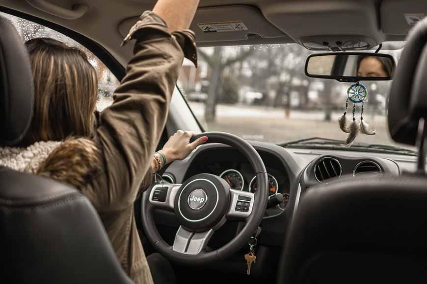 Prikaz žene za volanom sa udzignutom rukom