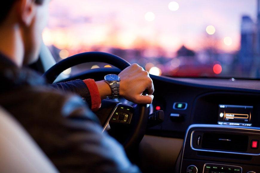 Unutrašnjost automobila sa vozačem koji se drži za volan